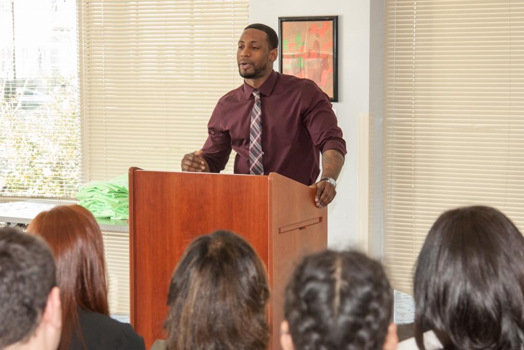 Building Pathways graduate speaks at podium