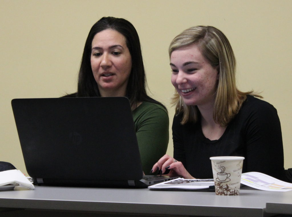 two women look at laptop