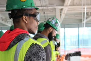 young men in construction hats look over railing
