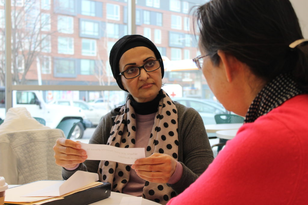 woman in headscarf holds slip of paper, facing another woman