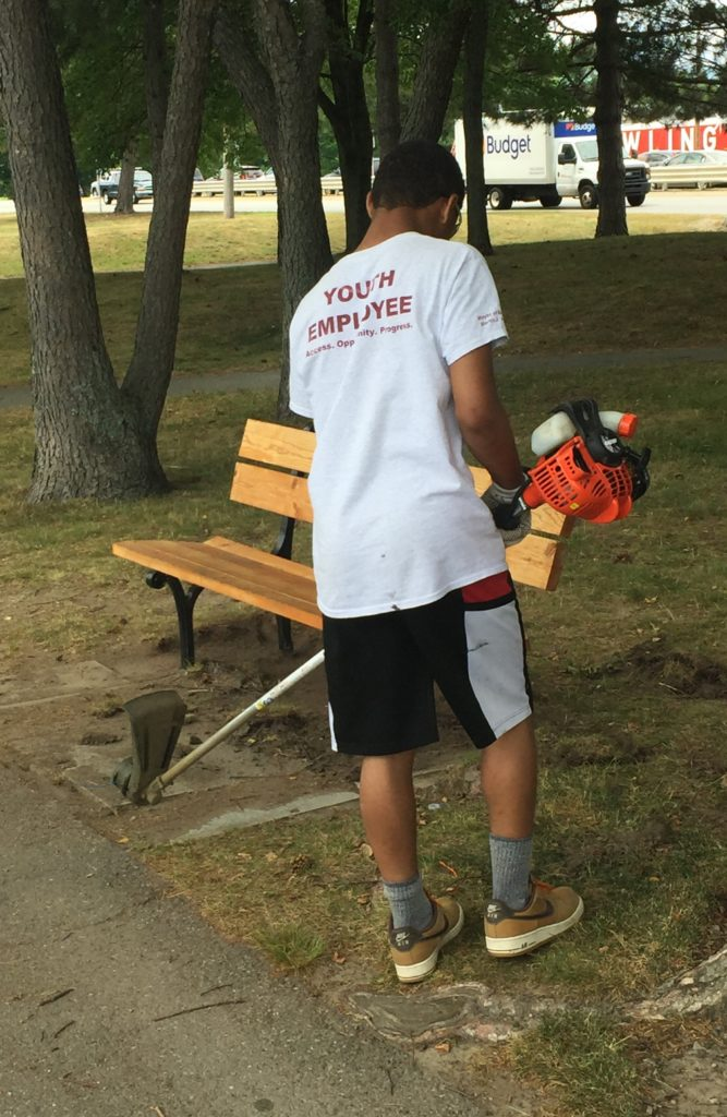 "black teen wearing ""Youth Employee"" T-shirt trims weeds around a bench"