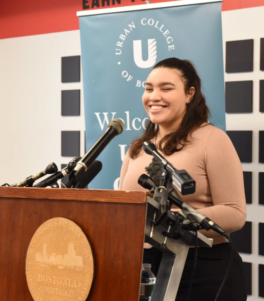 Student smiling at the podium, surrounded by microphones.